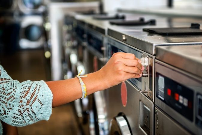 Woman putting a coin in a laundry machine